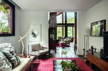 Sala de TV com pontrona Annette, de Jorge Zalszupin e luminária de piso Urbano, em projeto do arquiteto David Guerra.